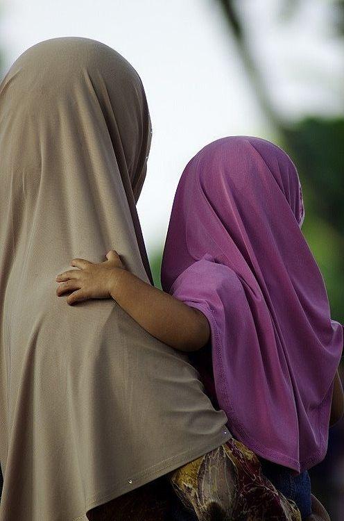 イスラム教徒の親子が向こう側を見ている写真です。