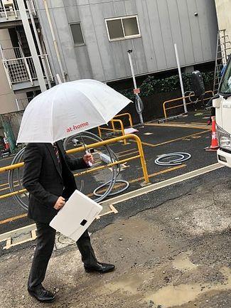 雨の中を歩くスタッフ
