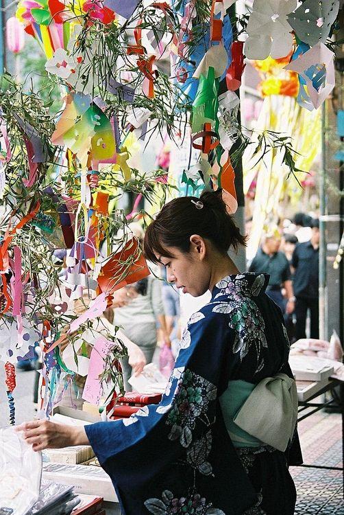 笹の葉に短冊をかける女性の写真です。