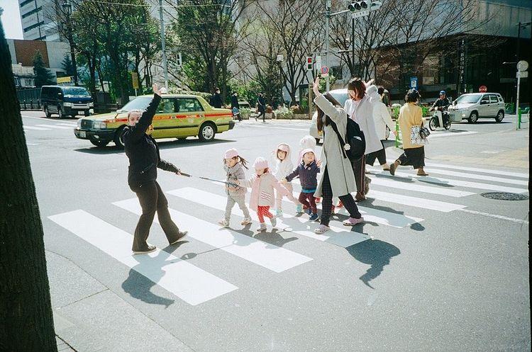 横断歩道を渡る園児たちの写真です。