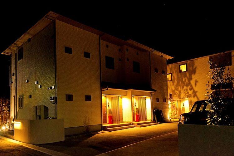 夜に撮影された築浅アパートの外観写真です。