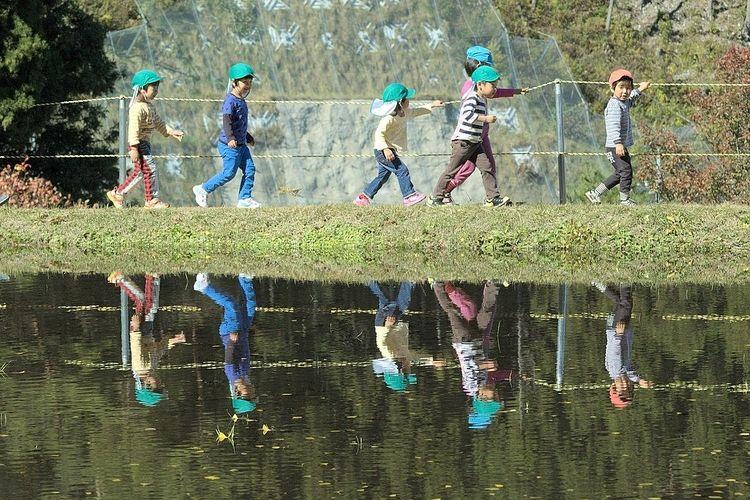 田んぼ脇を歩く児童たちの写真です。