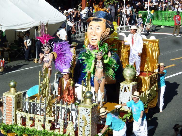 浅草サンバカーニバル、台車の上からダンサーの方が手を振っている写真です。