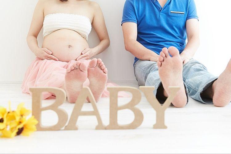 BABYの文字の後ろに、夫婦が横並びで座っている写真です。
