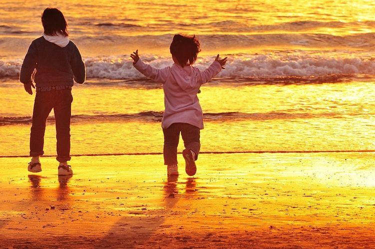 夕方の海に、子供二人が海岸に向かっている写真です。