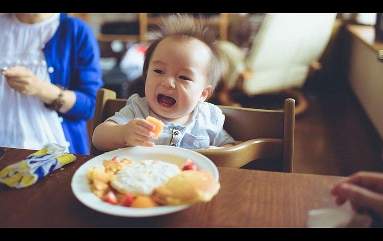 おやつを食べて喜んでいる赤ちゃんの写真です。